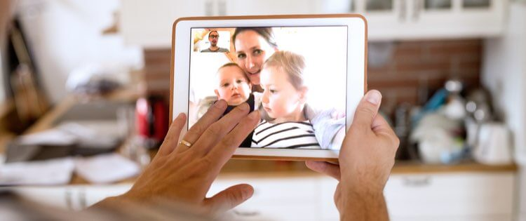 man video chatting with a woman and two children on a tablet device