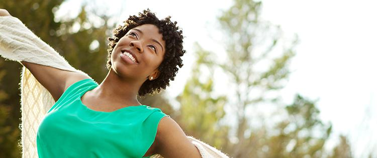 Photo of a smiling black woman with arms open wide