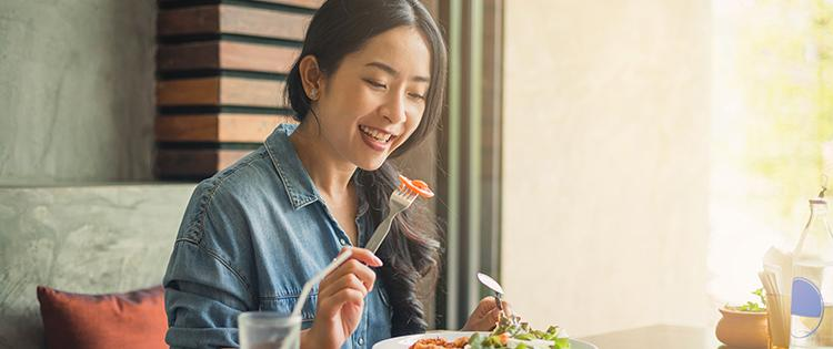 Photo of an Asian woman eating a salad at a restaurant