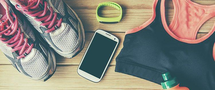 Photo of sneakers, a smartphone, a sports bra, and other workout gear laid out on a table