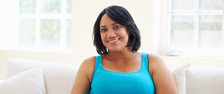 Photo of an African American woman smiling while sitting on a couch