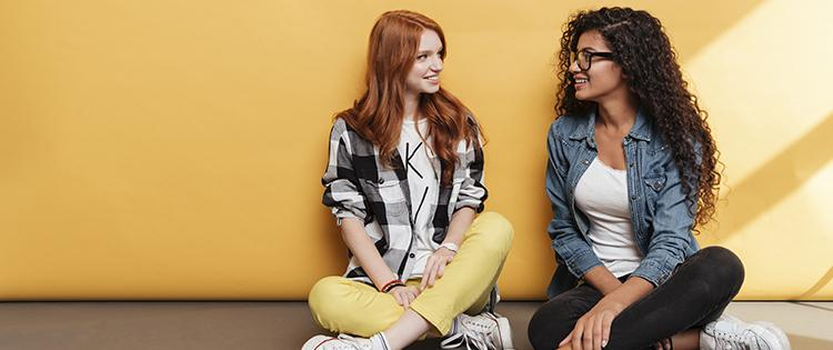 Photo of two young women sitting against a wall and talking.