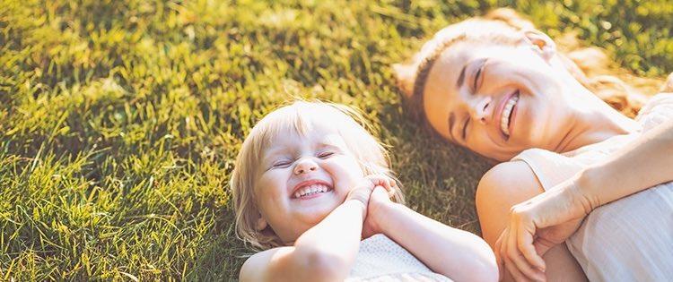 Photo a mother and her toddler smiling and laying on the grass outside