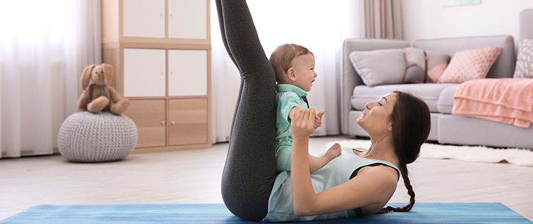 Photo of a woman on a yoga mat with her baby at home