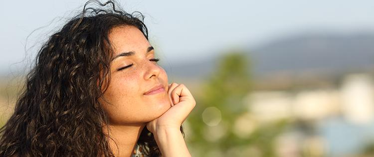 Woman of a young Hispanic woman sitting outside with her eyes closed