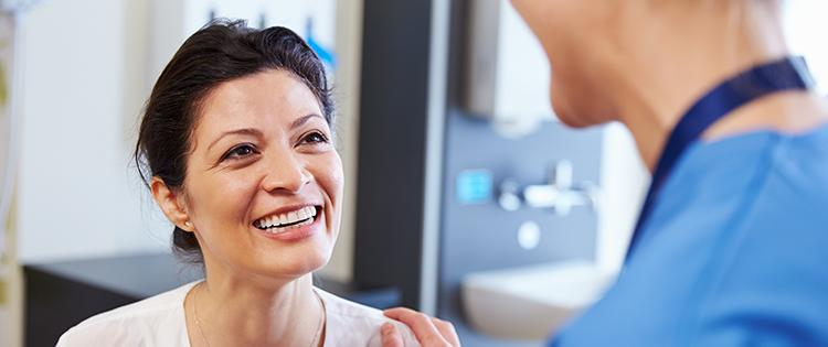 Photo of a dark haired middle aged woman talking to a healthcare provider