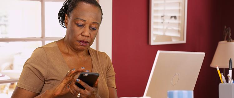 Photo of a middle aged black woman looking at her smartphone while sitting at her desk