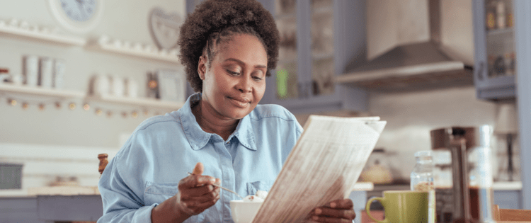 Photo of a middle aged black woman eating a healthy breakfast while reading the newspaper