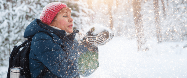 Photo of a middle aged woman blowing snow out of her hands