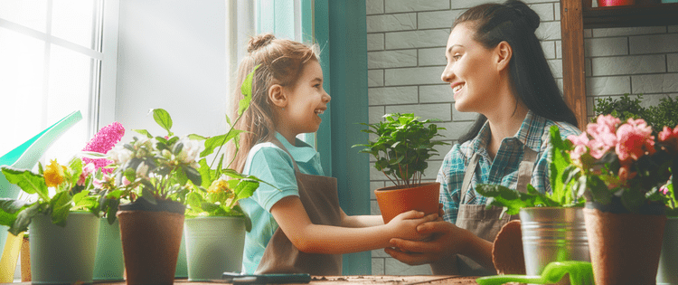 Photo of mother and daughter taking care of plants together