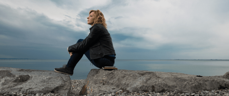 Photo of a blonde woman sitting on a rocky beach on a cloudy day.