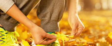 Photo of a woman tying her shoelaces surrounded by autumn leaves