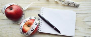 Photo of two apples, a notepad, and a tape measure