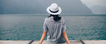 Photo of a woman wearing a hat while sitting on a pier and looking at the water.