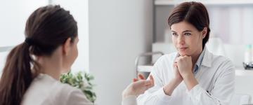 Photo of a woman speaking to a listening doctor