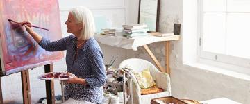 Photo of an older white woman painting in her studio
