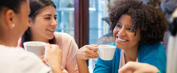 Photo of a diverse group of women talking while drinking coffee