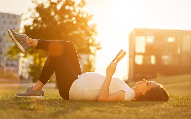 Photo of a pregnant woman reading a book while lying in the grass