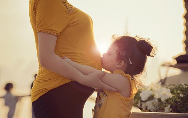 Photo of a young girl kissing her mother's pregnant stomach