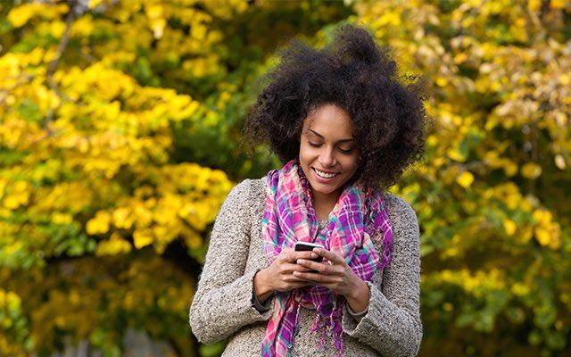 Photo of a young black woman looking at her smartphone outside