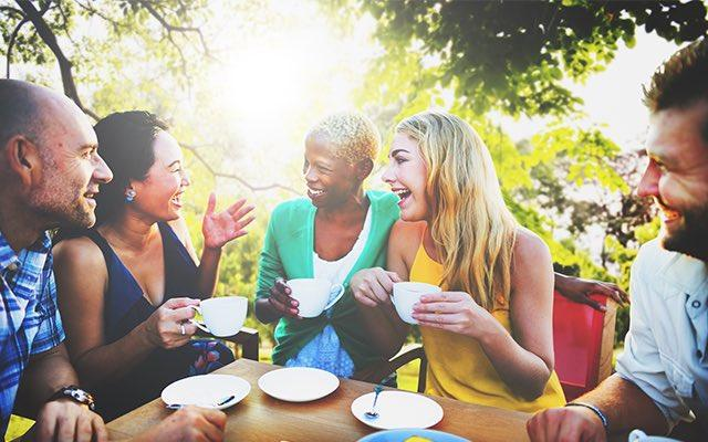 Photo of diverse group of adult enjoying coffee outside
