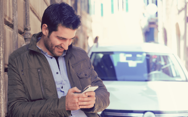 Photo of dark haired man using his smartphone while standing outside near a car