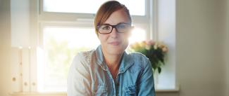 Photo of a women wearing glasses sitting in front of a window in her home