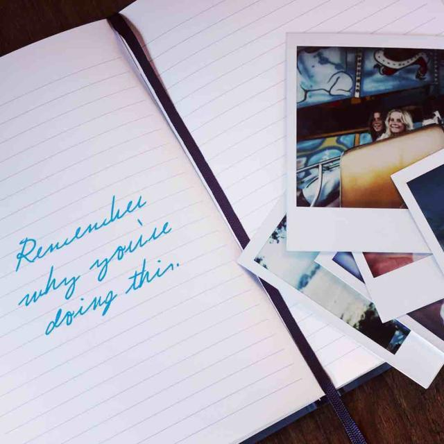 "Photo of a notebook and some photographs with ""Remember why you're doing this"" written in the notebook"
